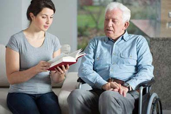 Home health aide reading to elderly man