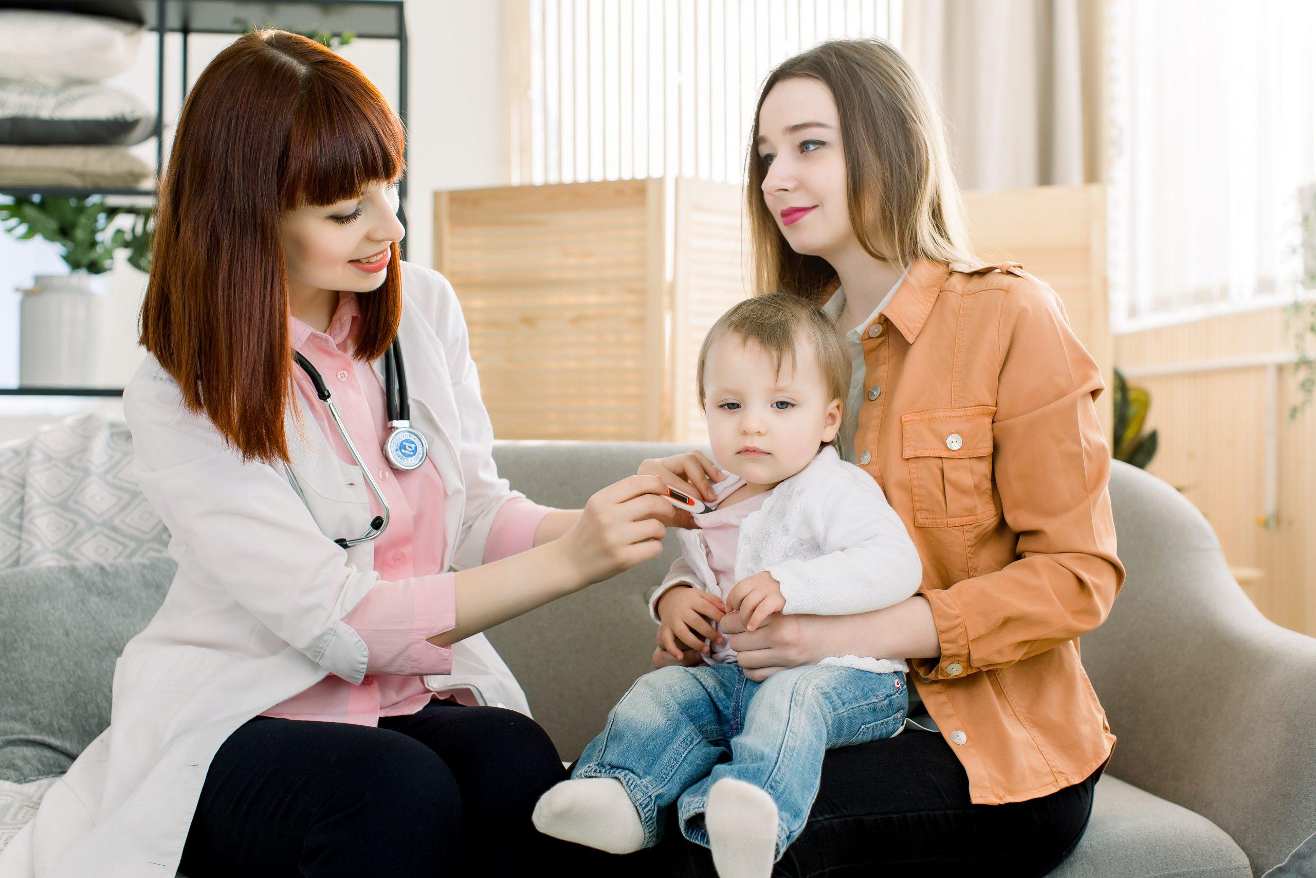 Baby having temperature taken by nurse